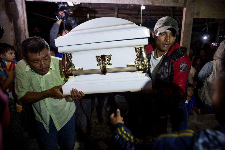 Buren en familieleden dragen in het Guatemalteekse dorp San Antonio Secortez de kist met daarin het lichaam van de 7-jarige Jakelin Caal het huis van haar grootouders in.