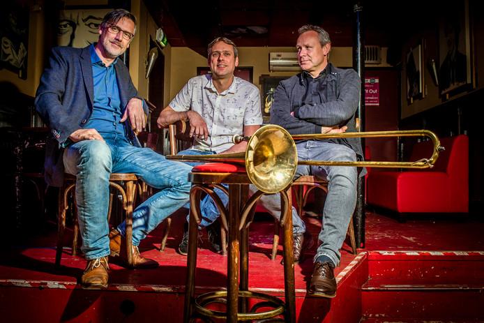 De broers (v.l.n.r.) Paul, Guus en Jasper de Waal op het podium van cafe 't Slik, waar hun vader vaak heeft gestaan. Voor hun op de kruk de trombone waarop hun overleden vader Guus de Waal sr. vaak heeft gespeeld.