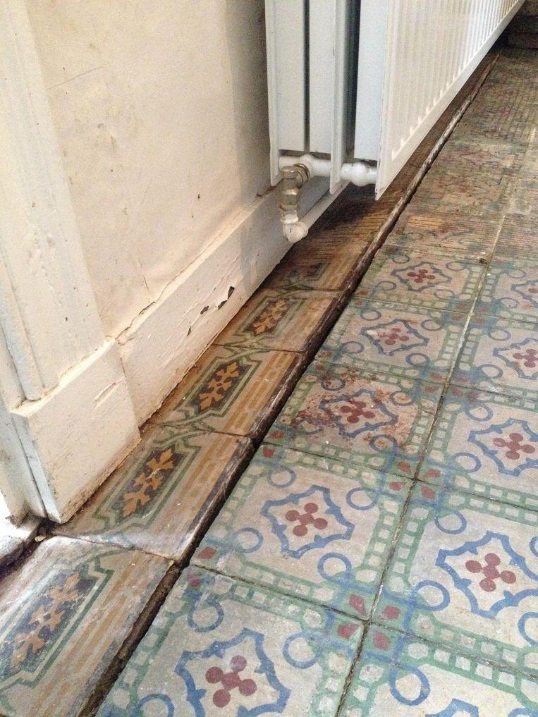 De scheur in de vloer en de scheefgezakte tegels.