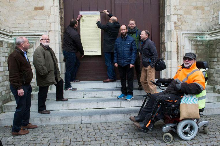 Actievoerders hangen traktaten op aan de kerk tegen de naamswijziging.