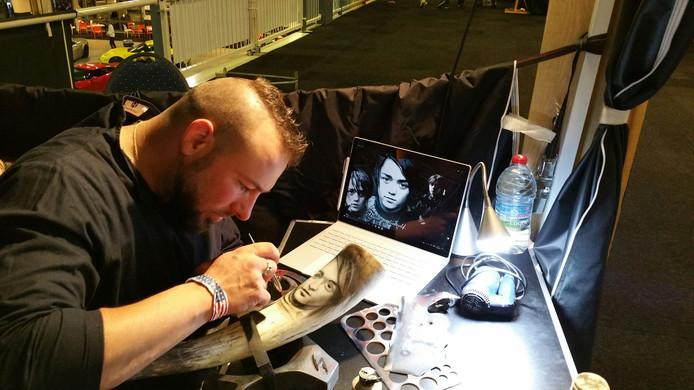Sébastien Guillaumont bewerkt een hoorn met Airbrush.