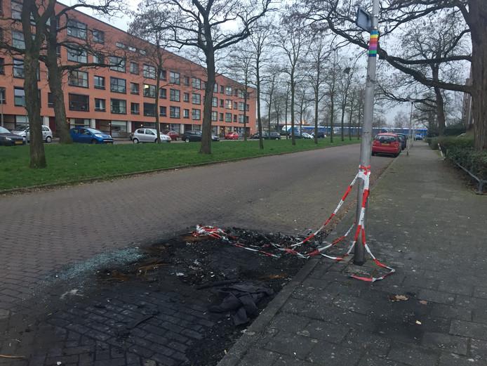 De brandresten en de rode politielinten markeren de plek waar op 4 februari een auto uitbrandde aan de Schorpioenstraat.