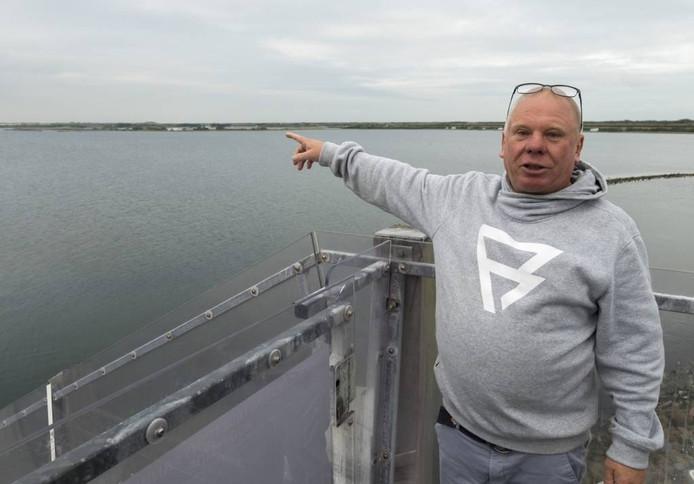 Uwe Jendrusch, eigenaar van zeil- en surfcentrum Brouwersdam, vreest het einde van de surfbaai -en dus van zijn bedrijf- als het project Brouwerseiland doorgaat. Zeker als ook de Middelplaat, waarnaar hij op deze foto wijst, ook wordt bebouwd. Foto Dirk-Jan Gjeltema