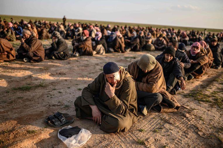 Deze mannen worden ervan verdacht voor IS te hebben gevochten. Ze worden gevangen gehouden door de door Koerden geleidde SDF. Beeld AFP