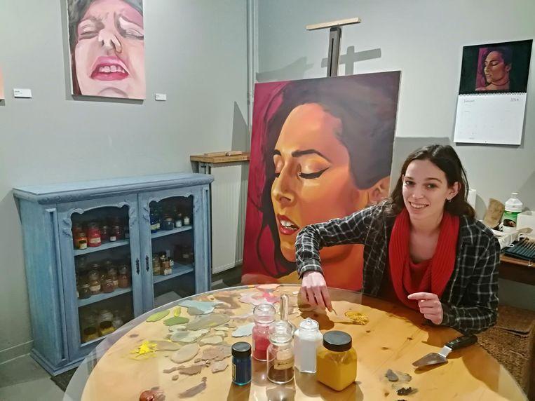 Khiara mengt de kleuren voor haar volgende schilderij.