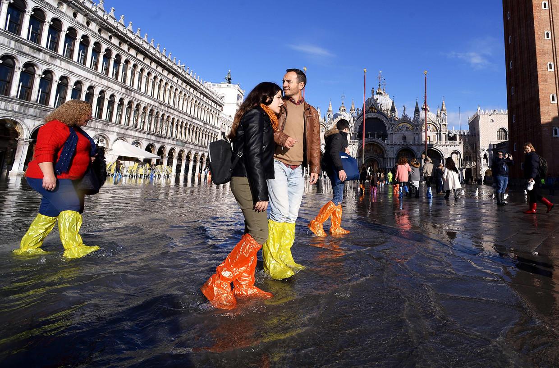 Toeristen lopen over het San Marcoplein in Venetië, waar het water sinds 1966 niet zo hoog heeft gestaan.
