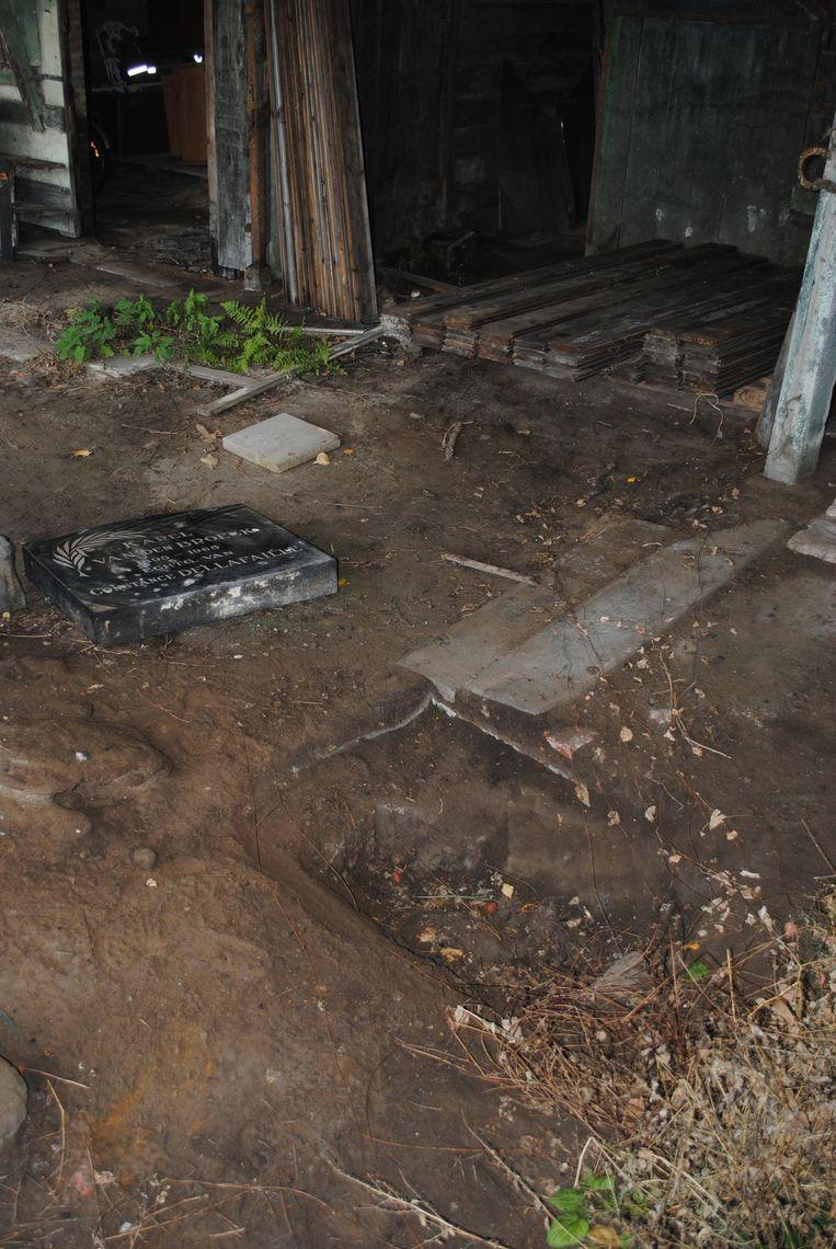 Rond de grafsteen lag heel wat rommel waardoor hij niet meteen opviel