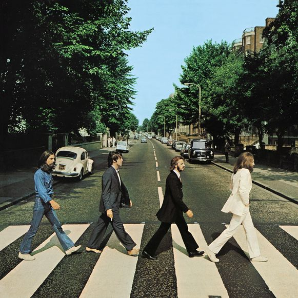 Op 8 augustus 1969 om 10 uur wandelen - van links naar rechts - George Harrison, Paul McCartney, Ringo Starr en John Lennon over het bewuste zebrapad. McCartney heeft z'n sandalen uitgeschopt, omdat het bloedheet is.