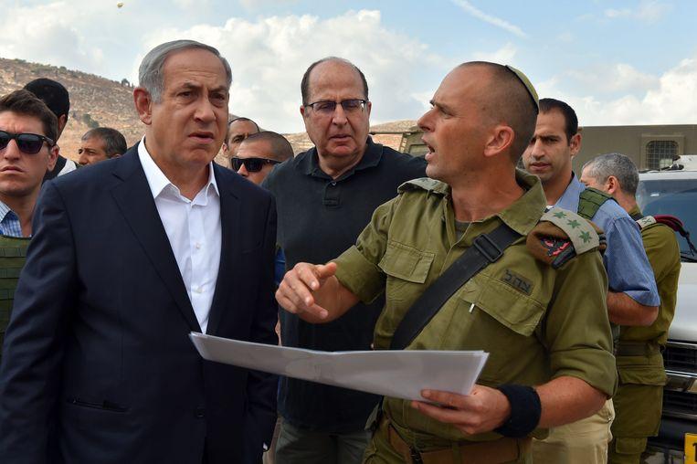 Premier Netanyahu (links) en defensieminister Moshe Yaalon (midden) krijgen uitleg van een legerofficier tijdens een bezoek aan de plek waar op 1 oktober een ISraëlisch koppel werd gedood.