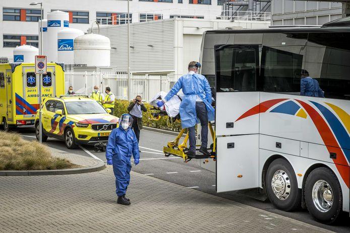 Een patiënt wordt uit de speciale ambulancebus gehaald, die met zes coronapatiënten naar academisch ziekenhuis Maastricht UMC+ is gereden. De patiënten zijn afkomstig uit Rotterdam.