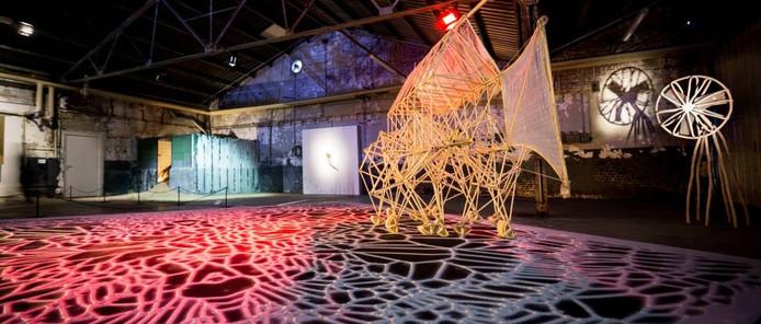 Beeld van de expositie Maarten Baas makes time met werk van o.a. Baas zelf (rechts) en een Strandbeest van Theo Jansen op een zandtapijt van Iris van Herpen. foto Nick Bookelaar
