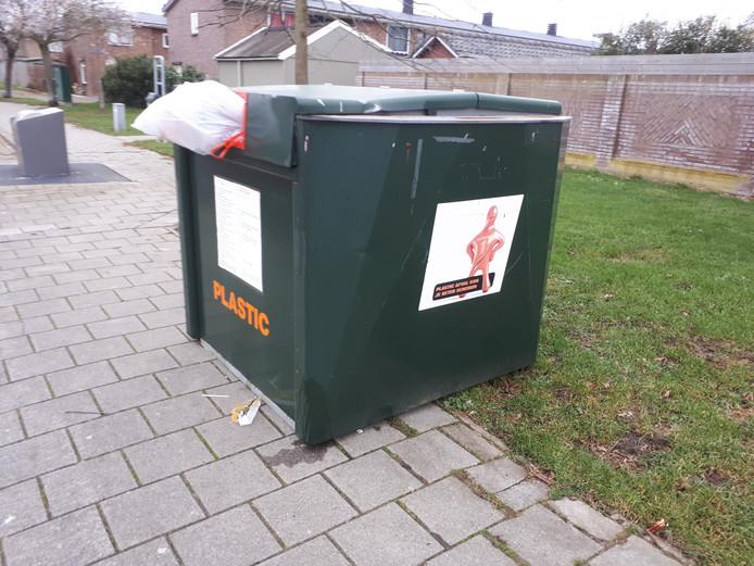 De tijdelijke plastic-container aan de Kamperfoeliestraat, waar donderdagmiddag alweer een te grote zak uitstak.