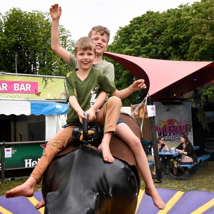 Tibbe (voor) en Brammert de Ruijter vermaken zich zondagmiddag op de rodeostier tijdens het Lentefestival op het Exercitieveld in Woerden.