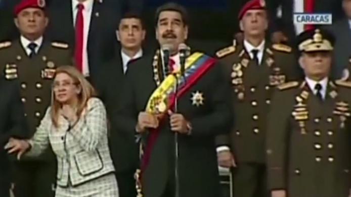 De vrouw van Maduro kijkt verschrikt omhoog nadat explosies hebben geklonken.