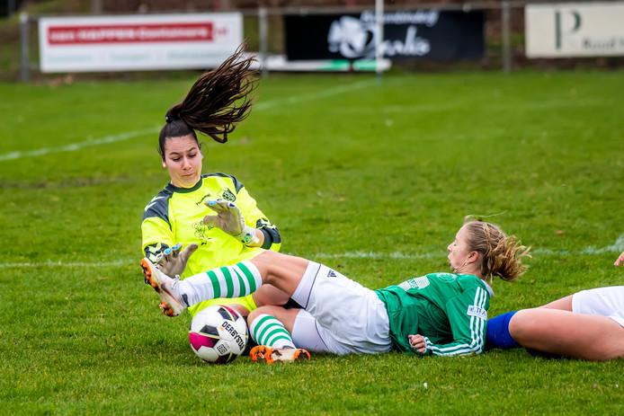 In een uiterste poging om bij de bal te komen vindt Ilse van der Heijden (midden) de doelvrouw van SV Venray op haar pad.