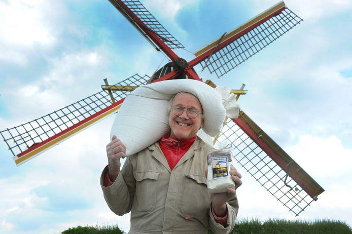 Sjaak Brasser, met op de achtergrond de Korenmolen in Biggekerke, met meel voor het maken van bolussen.