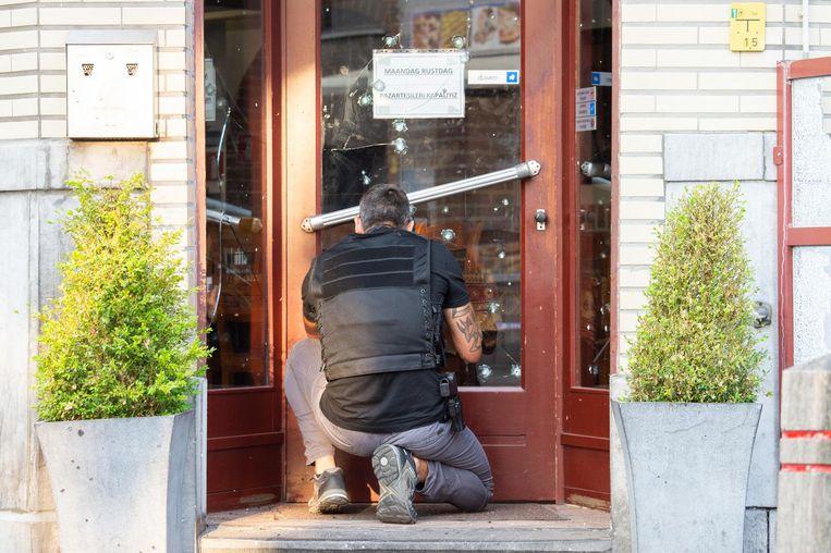 Een agent onderzoekt de deur van de zaak op mogelijke sporen.