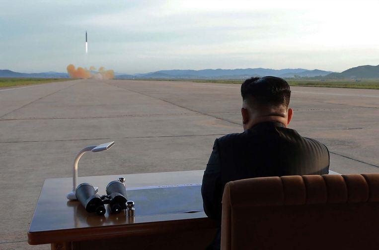 Noord-Korea's leider Kim Jong-un slaat in 2017 de lancering van raket Hwasong-12 gade. Beeld AFP