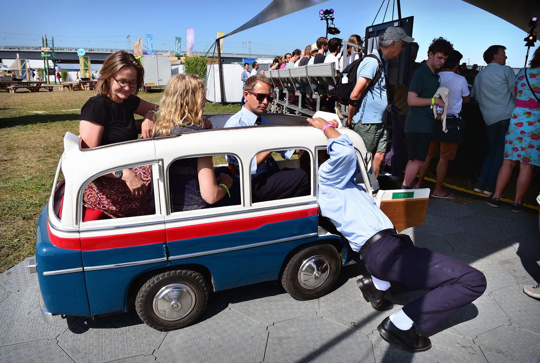 Bezoekers van het Democratiefestival. Met een alternatief pendelbusje kunnen ze van plek naar plek op het Waal-eiland Veur-Lent in Nijmegen.