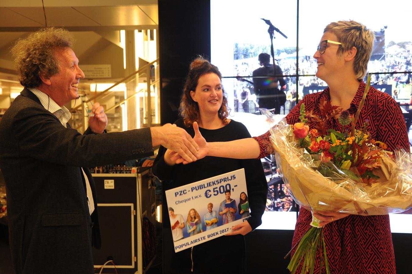 PZC-journalist Jan van Damme overhandigt de PZC-Publieksprijs aan Karlijn de Splenter (midden). Vormgeefster Corinne Lecluyse neemt de bloemen in ontvangst. Het jubileumboek Weitjerock kreeg de meeste stemmen: 368.
