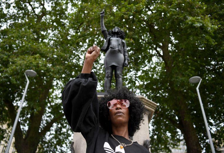 Activist Jen Reid poseert bij het standbeeld van Marc Quinn. Beeld EPA