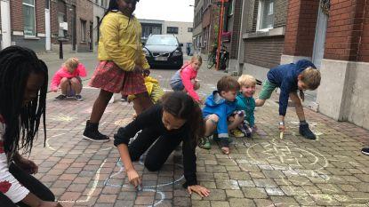 Kinderen maken krijttekeningen tegen haat in de Weverijstraat, buren delen 'Zonder haat straat'-affiches uit
