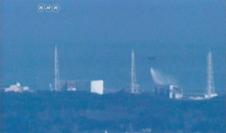 Een militaire helikopter dropt water op Fukushima. Beeld reuters
