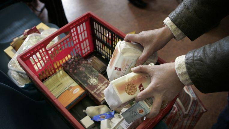 Het elftal begint het met uitdelen van voedselpakketten aan klanten van de voedselbank. Beeld ANP