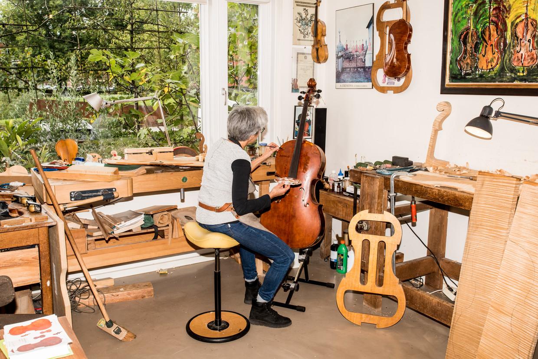Saskia Schouten, viool- en cellobouwer, lakt in haar atelier Den Bosch het voorblad van een cello. Beeld Jan Mulders
