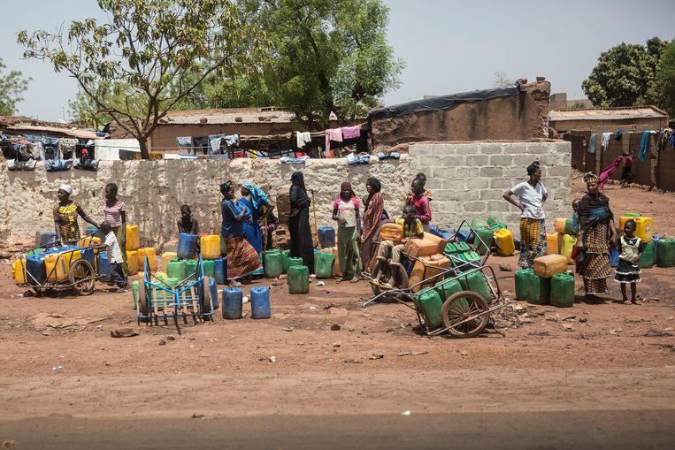 Vrouwen met jerrycans om water mee te vervoeren in de Malinese hoofdstad Bamako. Beeld Getty Images