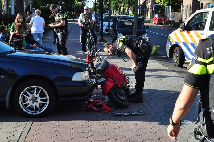 De politie probeert de aangereden scooter uit te krijgen.