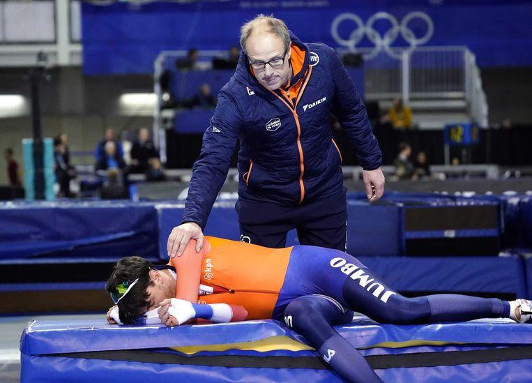 Patrick Roest wordt na zijn teleurstellende race getroost door trainer Jac Orie. Beeld ANP