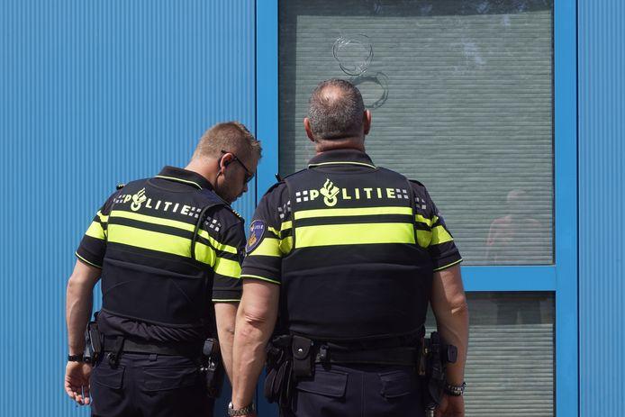 Agenten bekijken de gaten in het raam van de vereniging.