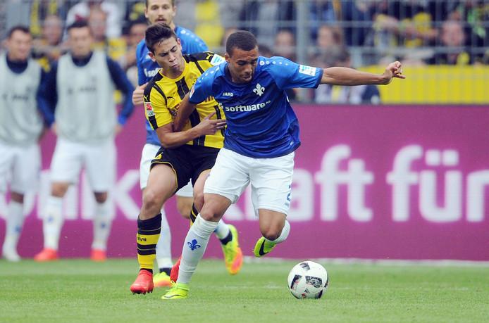 Leon Guwara op archiefbeeld uit 2016 namens Darmstadt in duel met Raphael Guerreiro van Borussia Dortmund.