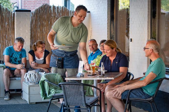 Dennis Brok serveert buiten op het terras van Brasserie de VOC.