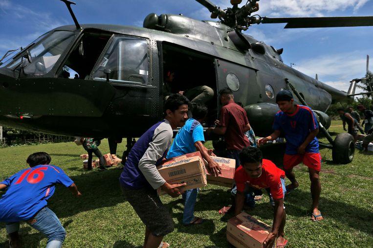 Overlevenden slepen met hulpgoederen die aangeleverd zijn door een Indonesische hulphelicopter.  Beeld AP