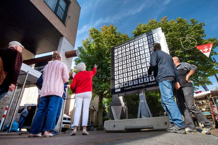 Het herdenkingsbillboard in de Langestraat in Huissen trekt direct al belangstellenden. Foto: Gerard Burgers.
