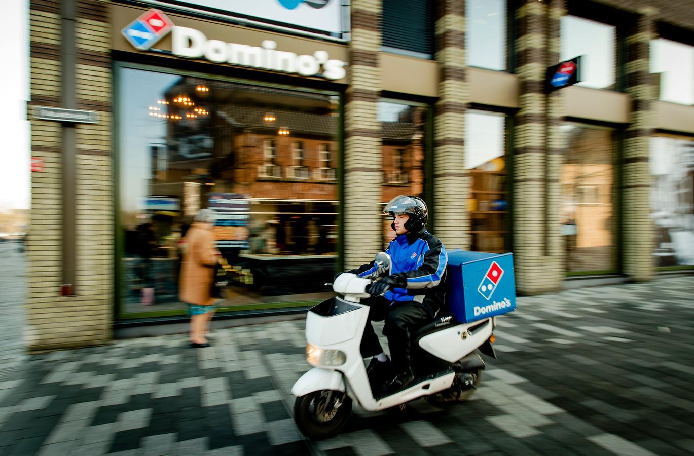 Foto ter illustratie. Een bezorger van pizzaketen Domino's