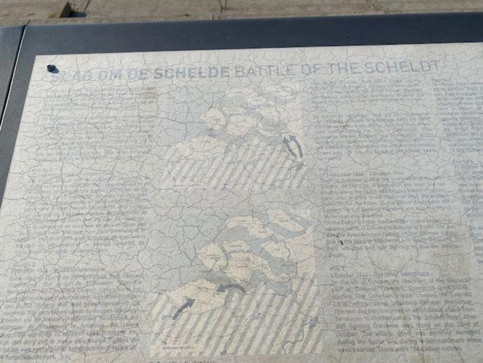Het informatiepaneel over de Slag om de Schelde is nog amper leesbaar door erosie.