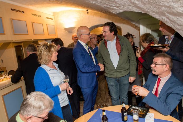 De allerlaatste vergadering van de gemeenteraad Neerijnen is een feit en er wordt afscheid genomen in de kelder van het gemeentehuis met een hapje en een drankje. Neerijnen valt binnenkort onder de gemeente West Betuwe. Burgemeester Harry de Vries (lichtblauw pak) praat nog even na met een aantal raadsleden.