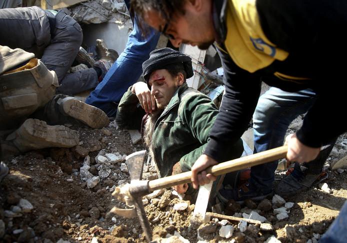 Een Syrische man zit vast in het puin van zijn huis na een luchtaanval bij Saqba, in de oostelijke buitenwijk van Damascus. Reddingswerkers weten hem na uren graven te bevrijden. Foto Bassam Khabieh
