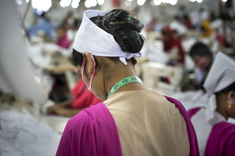 Werkneemster in een textielfabriek in Gazipur. De fabriek, Mark Mode, heeft 850arbeidsters in dienst en levert aan Europese bedrijven. Beeld Catrien Ariens
