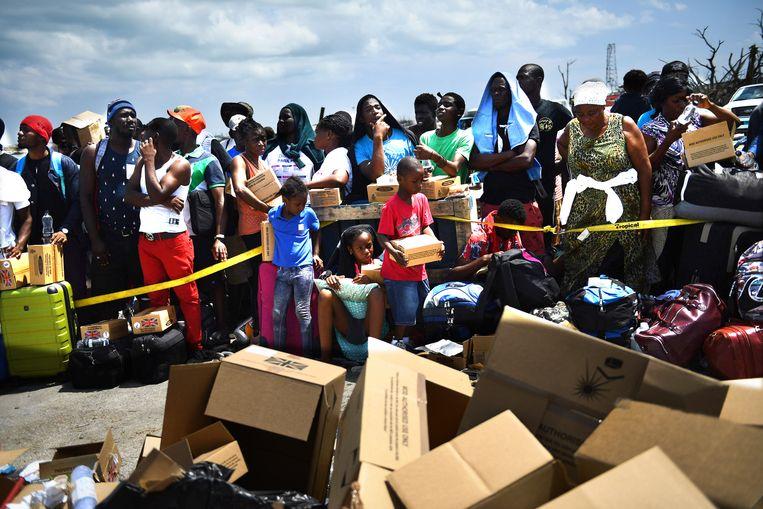 Mensen wachten in de haven van Marsh Harbour op evacuatie.  Beeld AFP