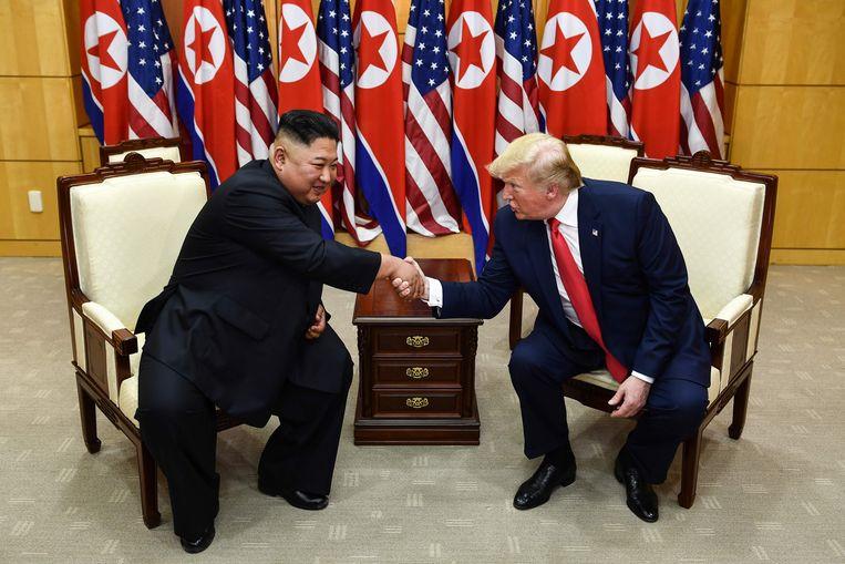 Trump en Kim Jong-un schudden elkaar de hand. Beeld AFP