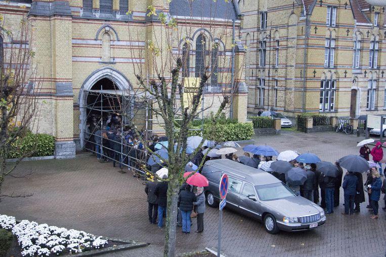 Aan de Sint-Gaugericuskerk van Pamel staat een lange rij wachtenden om de begrafenisplechtigheid voor Freddy Segers bij te wonen.