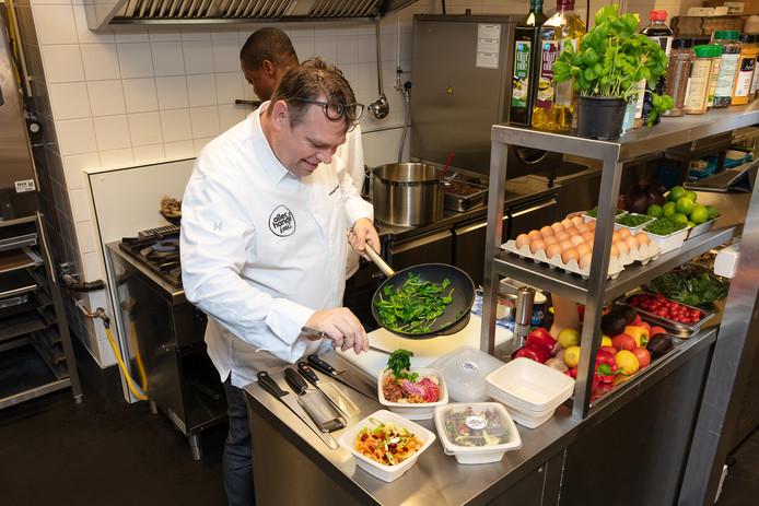 Koks van Allerhande bereiden maaltijden in de nieuwe keuken in Amsterdam.