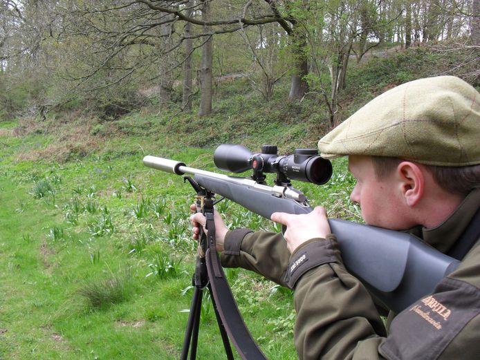 Een jager mét een geluidsdemper op de loop van het jachtgeweer.