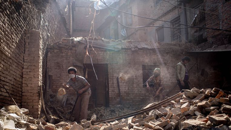 Inwoners van Kathmandu ruimen op in een huis dat door de aardbeving is getroffen. Beeld getty