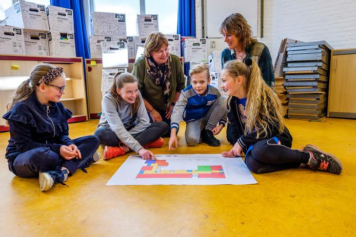 Noa (9), Noor (11), locatiedirecteur Irma van Eeken, Iloy (9), directeur Paulien Burgering, Sylvie (10) buigen zich over de nieuwe plattegrond van de Windroos.
