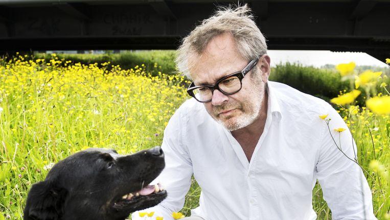 George van Houts met zijn hond in de Amsterdamse wijk IJburg. `Zelf kom je ook in de verleiding te gaan sjoemelen.' Beeld Sanne De Wilde